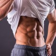 Man shows his abdominal muscles — Stock Photo #58921675