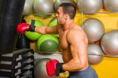 Muscular man in boxing gloves in gym — Stock Photo