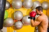 Muscular man in boxing gloves in gym — Stock fotografie
