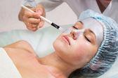 Young woman receiving facial mask — Stock Photo