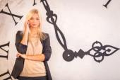 Woman standing near wall clock — Stockfoto