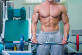 Man makes exercises with barbell — Stock Photo