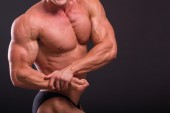 Athletic man showing muscles in suspense — Stock Photo