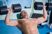 Bodybuilder makes exercises with dumbbells — Stock Photo