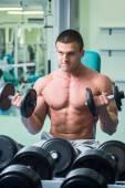Hombre en un gimnasio con pesas — Foto de Stock