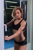 Sexy, blonde woman in the gym — Stock Photo