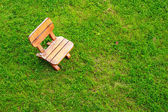 Wooden stool on green grass field — Stock Photo
