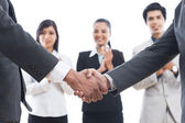 Two businessmen shaking hands with their colleagues applauding — Stock Photo