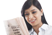 Close-up of a businesswoman reading a newspaper and smiling — ストック写真