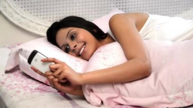 Woman text messaging in bed — Stock Video