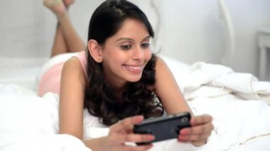Woman text messaging on bed — Stock Video