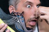 Piadas de homem depois de cheirar sapato — Fotografia Stock
