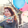 Beautiful woman with colorful balloons in the spring park — Stock Photo #71483379