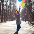 Beautiful woman with colorful balloons in the spring park — Stock Photo #71483397