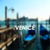 Vector illustration of gondolas in Venice lagoon, Italy. Blurred cityscape with typographic label — Wektor stockowy