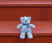 TEDDY BEAR blue color sitting on red staircase — Stock Photo