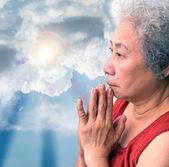 Mujer orando con el rayo de sol y cielo azul — Foto de Stock