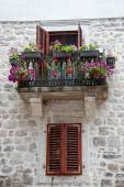Old balcony with flowers and window with shutters — Stockfoto