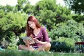 Girl sitting in the park studying with ipad — Stock Photo