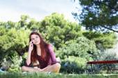 Girl sitting in the park with cell phone look up — Stock Photo