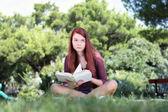 Estudante sentado no parque com um livro, olhando para cima — Foto Stock