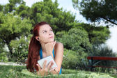 Estudante no parque com o livro digital e fones de ouvido — Foto Stock