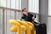 Businessman sitting talking on the phone and watching the clock, on a business travel — Stock Photo