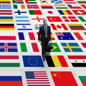 Business man travels the world, walking on a background of international flags — Stock Photo