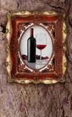 Bottle and glass wine in old picture frame on wood background — Stock Photo