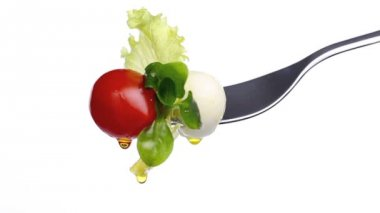 Fork lettuce salad leaves, tomato and mozzarella topped with olive oil isolated on white background — Stock Video