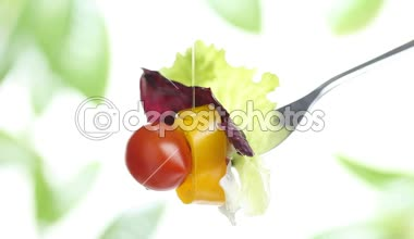 Fork lettuce salad leaves, tomato and pepper topped with olive oil isolated on white background — Stock Video
