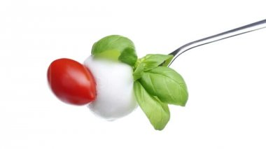 Fork tomato basil mozzarella topped with spilled oil isolated on white background — Stock Video