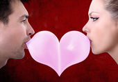 Lovers couple kiss heart shaped valentine day with chewing gum — Stock Photo