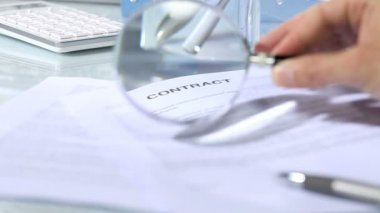 Looking through a magnifying glass to contract — Stock Video