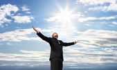 Business man on top of success, open arms to the sky — Stock Photo