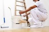 Painter man at work with a roller, bucket and scale, bottom view — Stock Photo