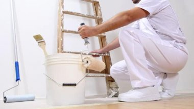 Painter man at work with a roller, bucket and ladder — Stock Video