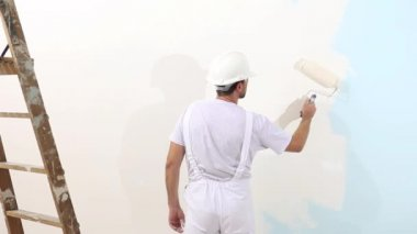 Painter man at work, with roller painting wall, painter house concept — Stock Video