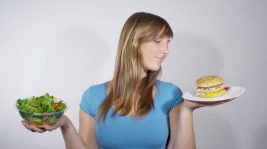 Woman choosing between fast and healthy food — Stock Video