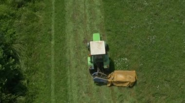 Flying above the tractor cutting grass — ストックビデオ