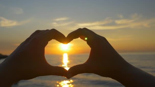Puesta de sol con las manos en forma de corazón — Vídeo de stock