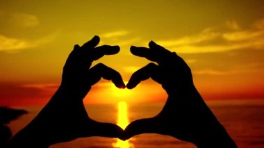 Sunset shining through heart shaped hands — Stock Video