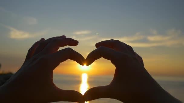 Captura el sol con el corazón en forma de manos — Vídeo de stock