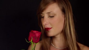 Woman smelling fragrant red rose — Stock video