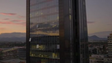 Flying around glass office building at sunset — Stock Video