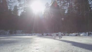 Female ice skating and spinning on frozen lake — Vídeo de Stock