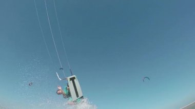Kiteboarder jumping and splashing water over camera — Stock Video