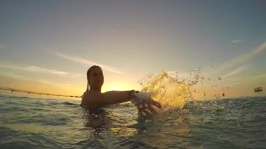 Woman splashing the water into camera — Stockvideo