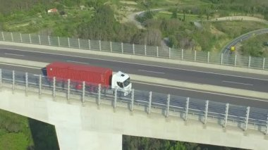 AERIAL: Container truck driving over the highway viaduct — Stock Video
