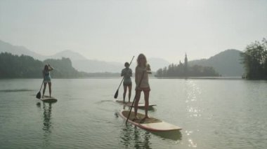 SLOW MOTION: Surfer girls SUPing on the beautiful lake at sunrise — Vídeo stock